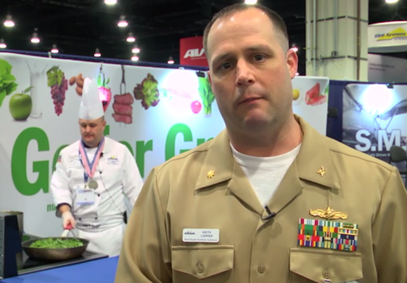 Still from video with sailor talking to camera and chef in background