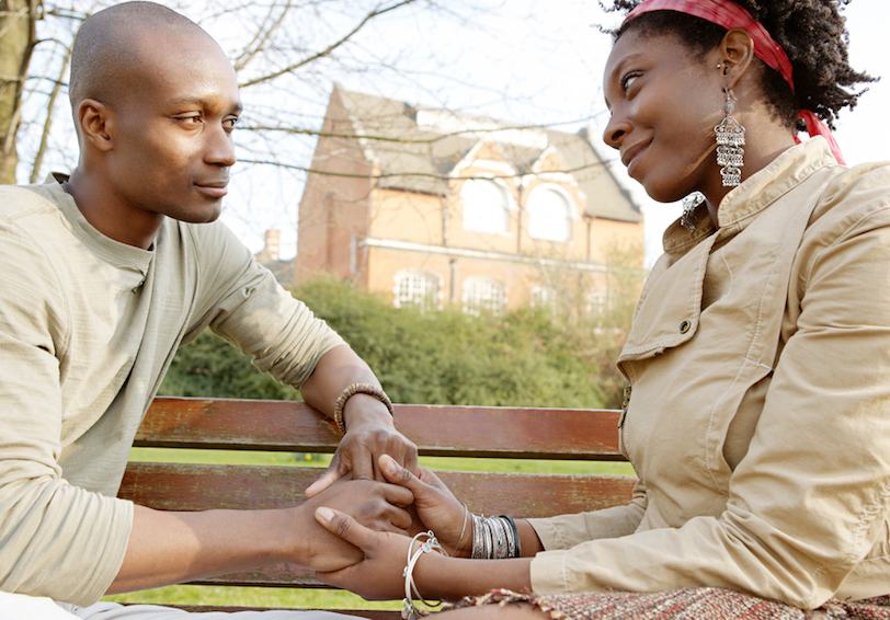 Man and woman holding hands on park bench.