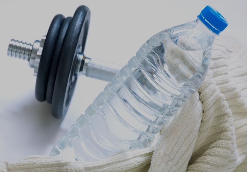 Hand weight, water bottle, and exercise towel on white background