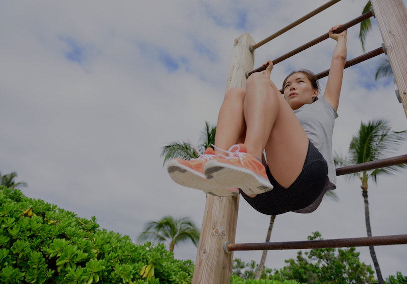 Woman doing core exercises outdoors on playground equipment