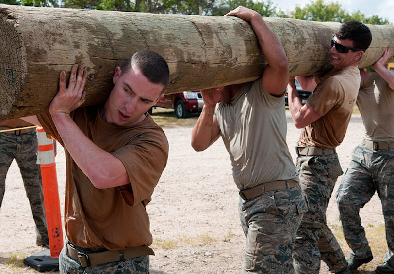 Group of airmen carrying heavy log together (U.S. Air Force photo by Airman 1st Class Malcolm Mayfield)
