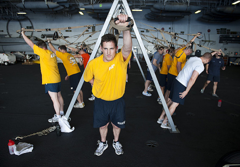 Sailors in group fitness class in hangar bay (U.S. Navy photo by Mass Communication Specialist 3rd Class Benjamin Crossley)