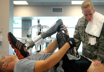 Soldier holding his prosthetic leg being examined by doctor
