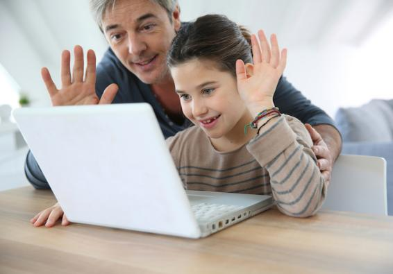Father and daughter waving at computer screen