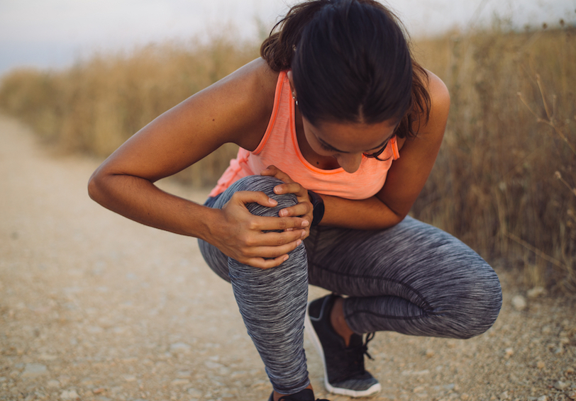 Woman in workout clothes kneeling down and holding knee in pain