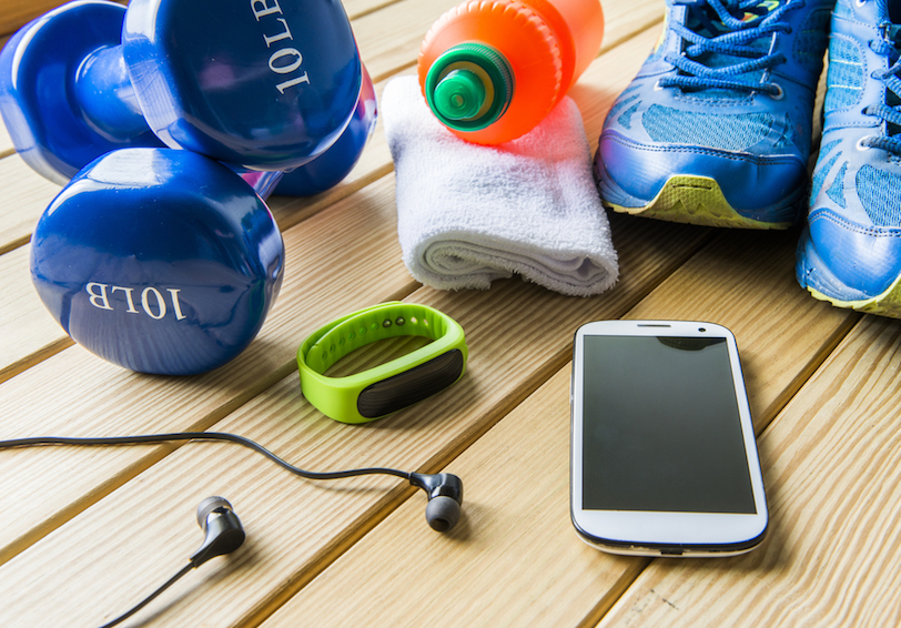Hand weights, water bottle, hand towel, running shoes, cell phone, activity tracker, and headphones on wooden surface