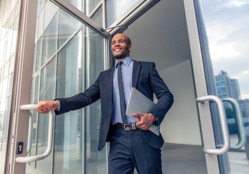 Smiling man in business suit walking out of glass door
