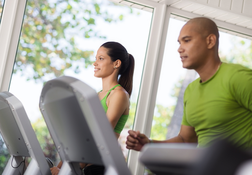 Man and woman running on treadmills.