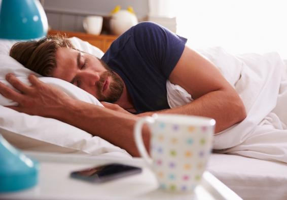 Man sleeping in bed with cup and phone on nightstand nearby
