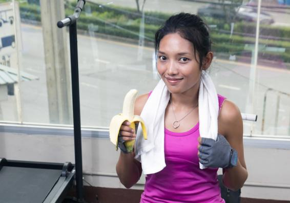 Woman getting ready to eat a banana after a workout