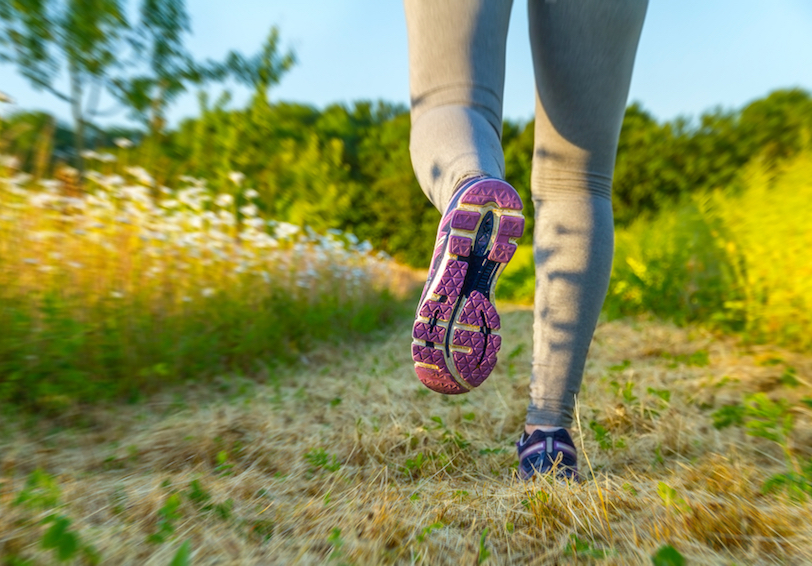 Legs of person running on grassy trail through wooded/grassy area