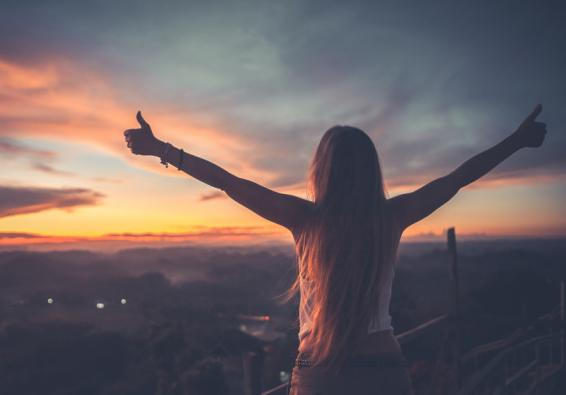 Woman looking at sunset raising arms and giving thumbs up