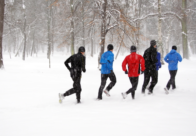 Group of people running in snowy wooded area