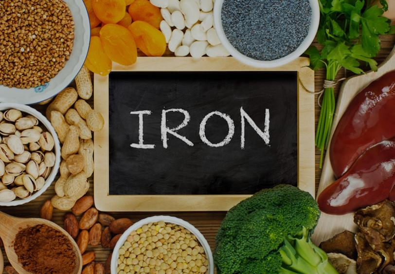 "Chalkboard with the word ""IRON"" surrounded by foods high in iron such as nuts and liver"