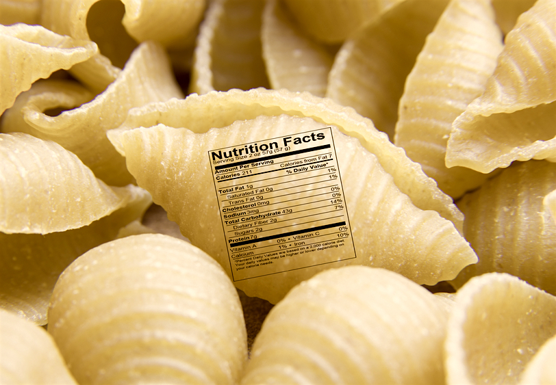 Close up of uncooked shell pasta noodle with nutrition label
